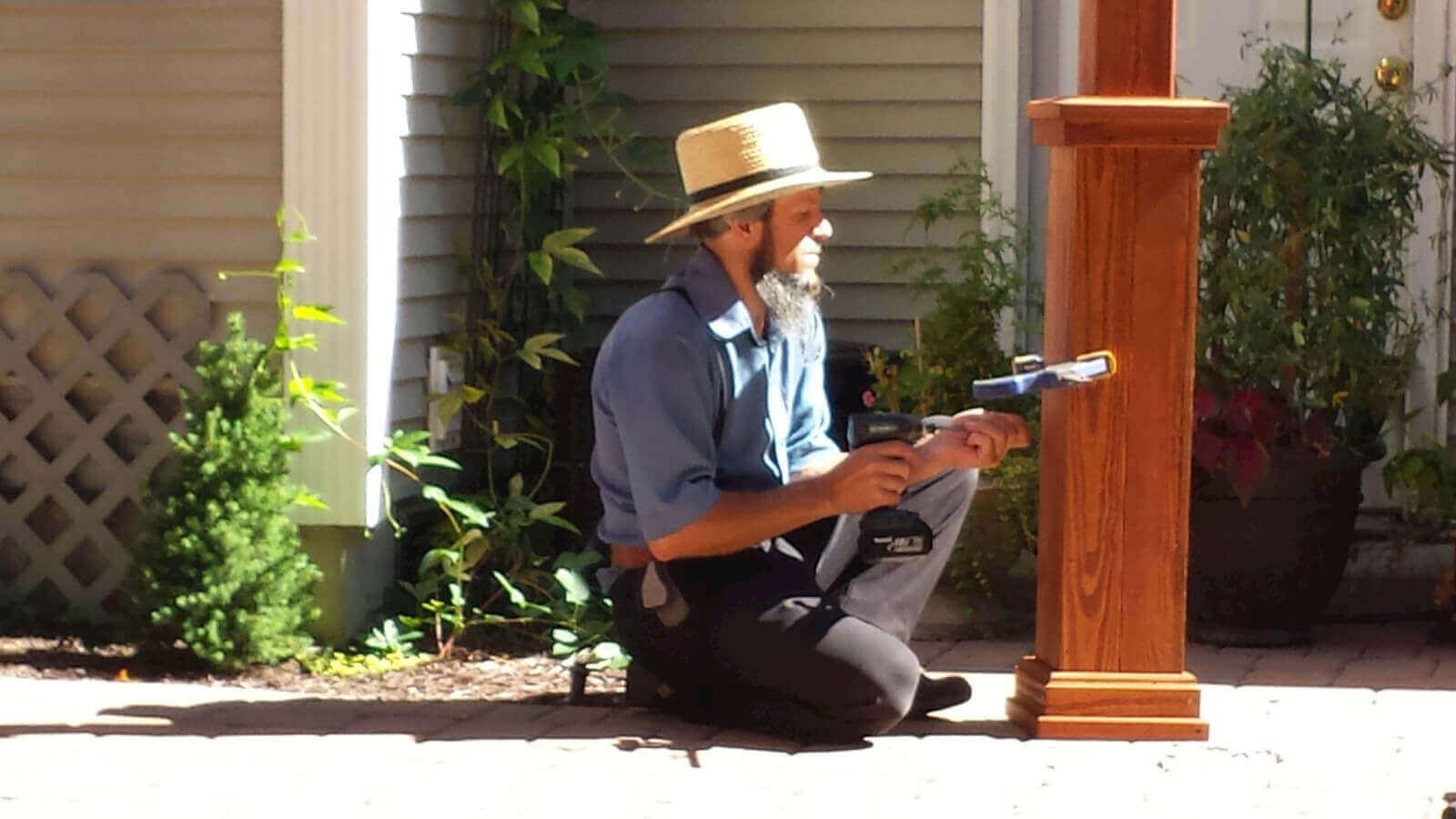 Amish worker installing a pergola